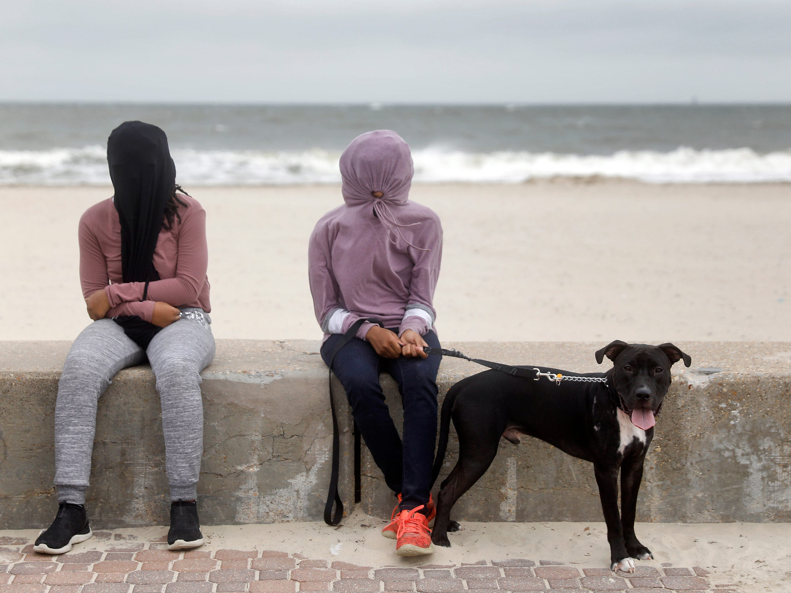 Josephine Mitchell, left, and Claudia Mitchell use clothing to cover their eyes as sand blows through the air at Buckroe Beach on Sept. 13, 2018.