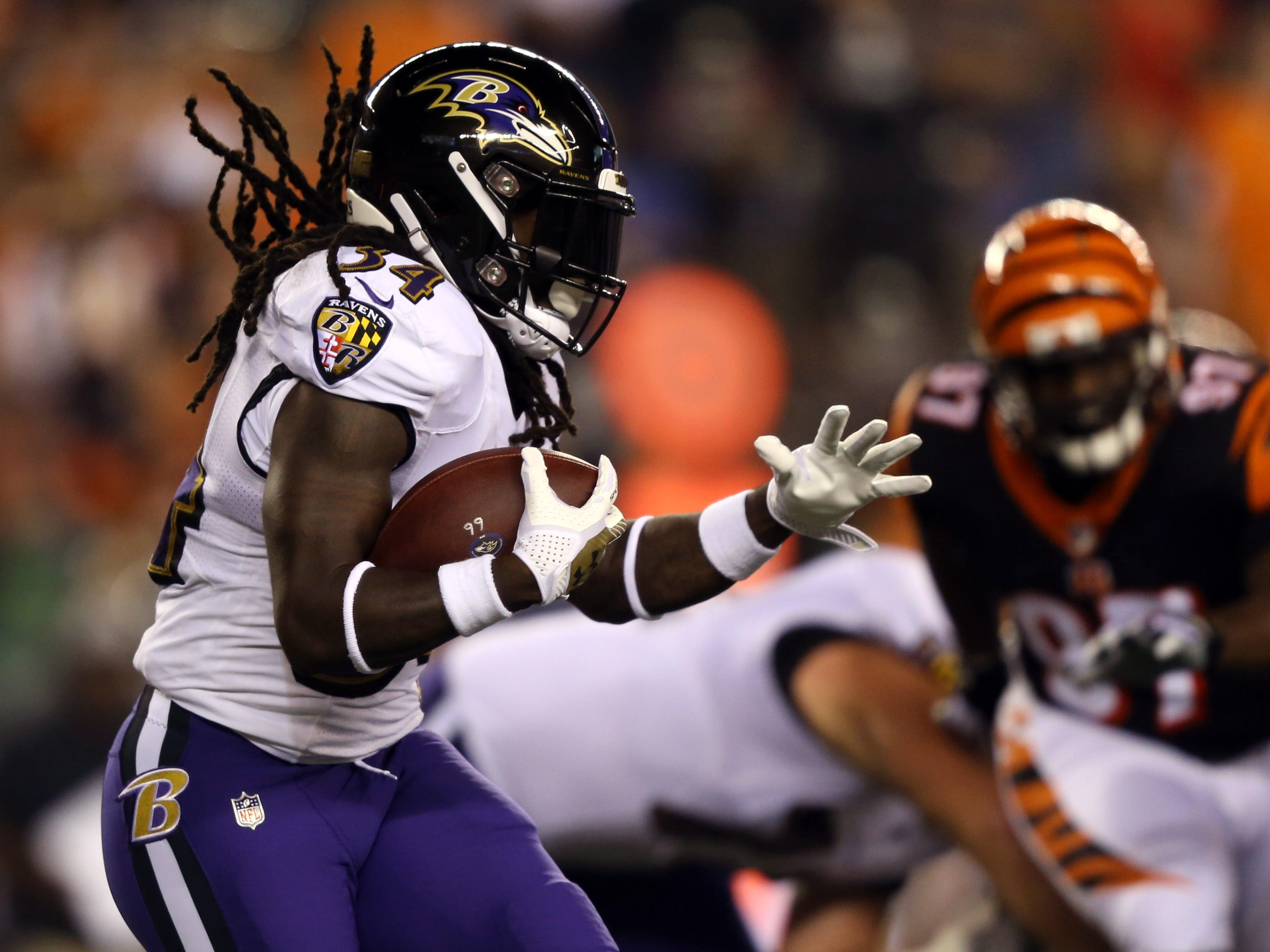 Ravens running back Alex Collins carries the ball against the Bengals in the first half at Paul Brown Stadium.