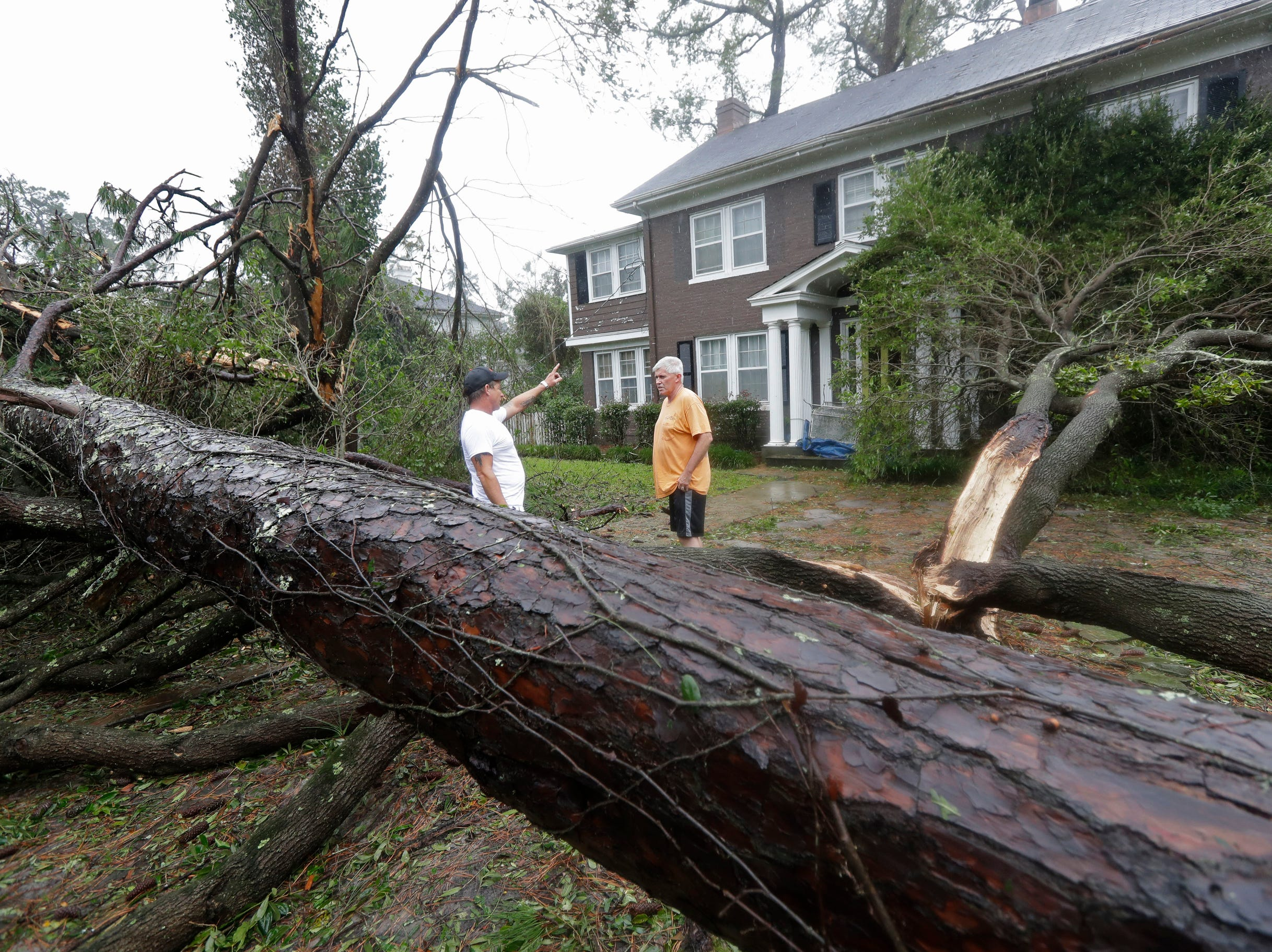 Chris Butcher, of Arborist Plus in Edgewood, Fla., talks with Mike Kiernan, right, about the damage to his home in Wilmington, N.C., after Hurricane Florence made landfall Friday.