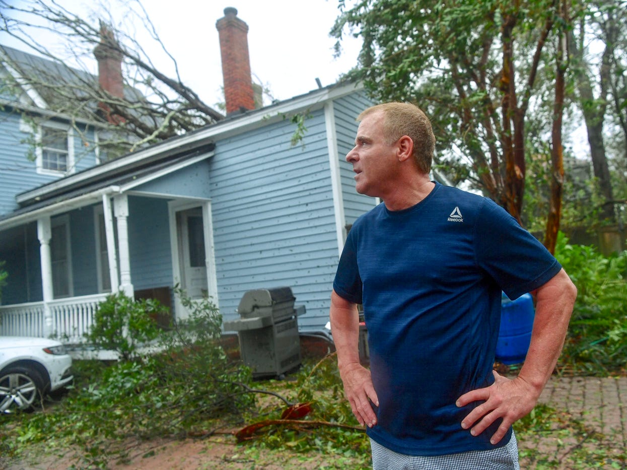 Charles Carver of Wilmington, N.C., looks at damage, a tree on his home, as Hurricane Florence passes through on Friday.