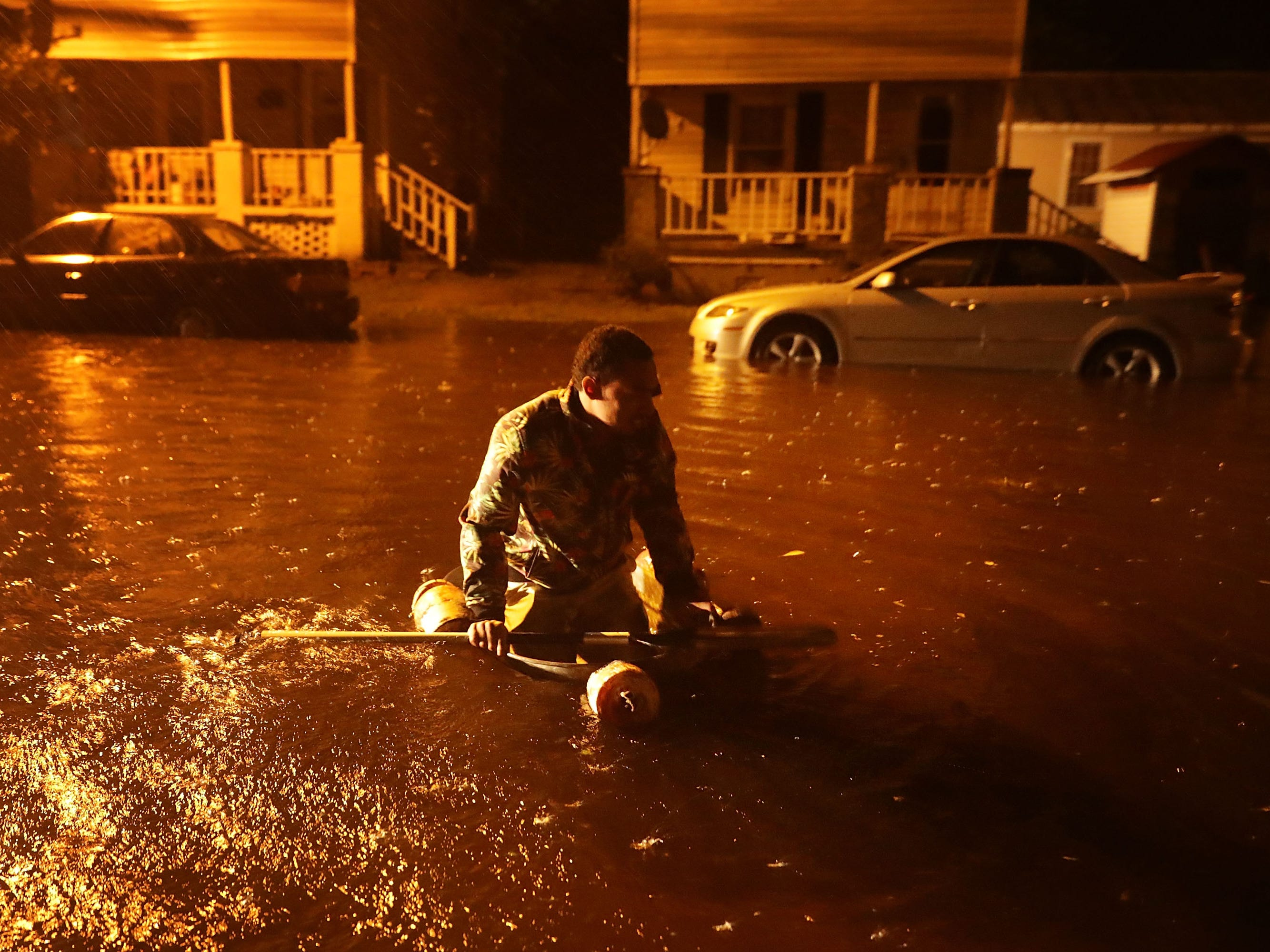 NEW BERN, NC - SEPTEMBER 13:  Michael Nelson floats in a boat made from a metal tub and fishing floats after the Neuse River went over its banks and flooded his street during Hurricane Florence September 13, 2018 in New Bern, North Carolina. Some parts of New Bern could be flooded with a possible 9-foot storm surge as the Category 2 hurricane approaches the United States.  (Photo by Chip Somodevilla/Getty Images) *** BESTPIX *** ORG XMIT: 775225768 ORIG FILE ID: 1032932662