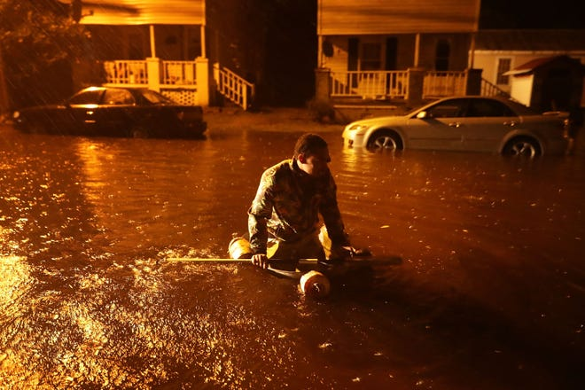 Michael Nelson floats in a boat made from a metal tub and fishing floats after the Neuse River went over its banks and flooded his street during Hurricane Florence on Thursday, Sept. 13, 2018, in New Bern, North Carolina.