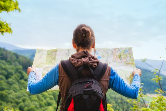 Woman Traveler With Backpack Checks Map To Find Directions In Wilderness Area Real Explorer Travel Concept