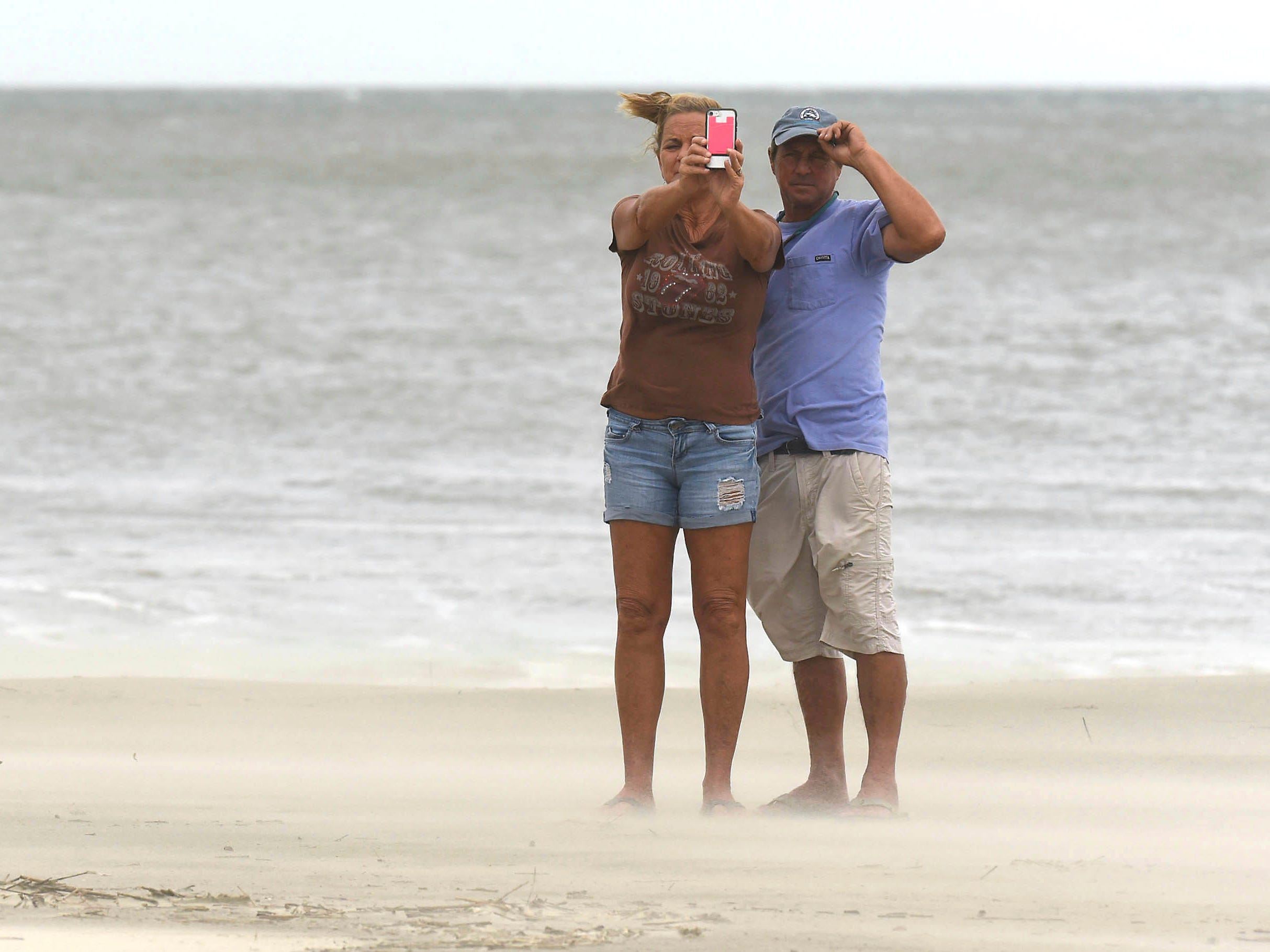 Sue and Kevin York take a selfie along the beach in Oak Island in Southport, N.C., as Hurricane Florence approaches the North Carolina coastline on Sept. 13, 2018.