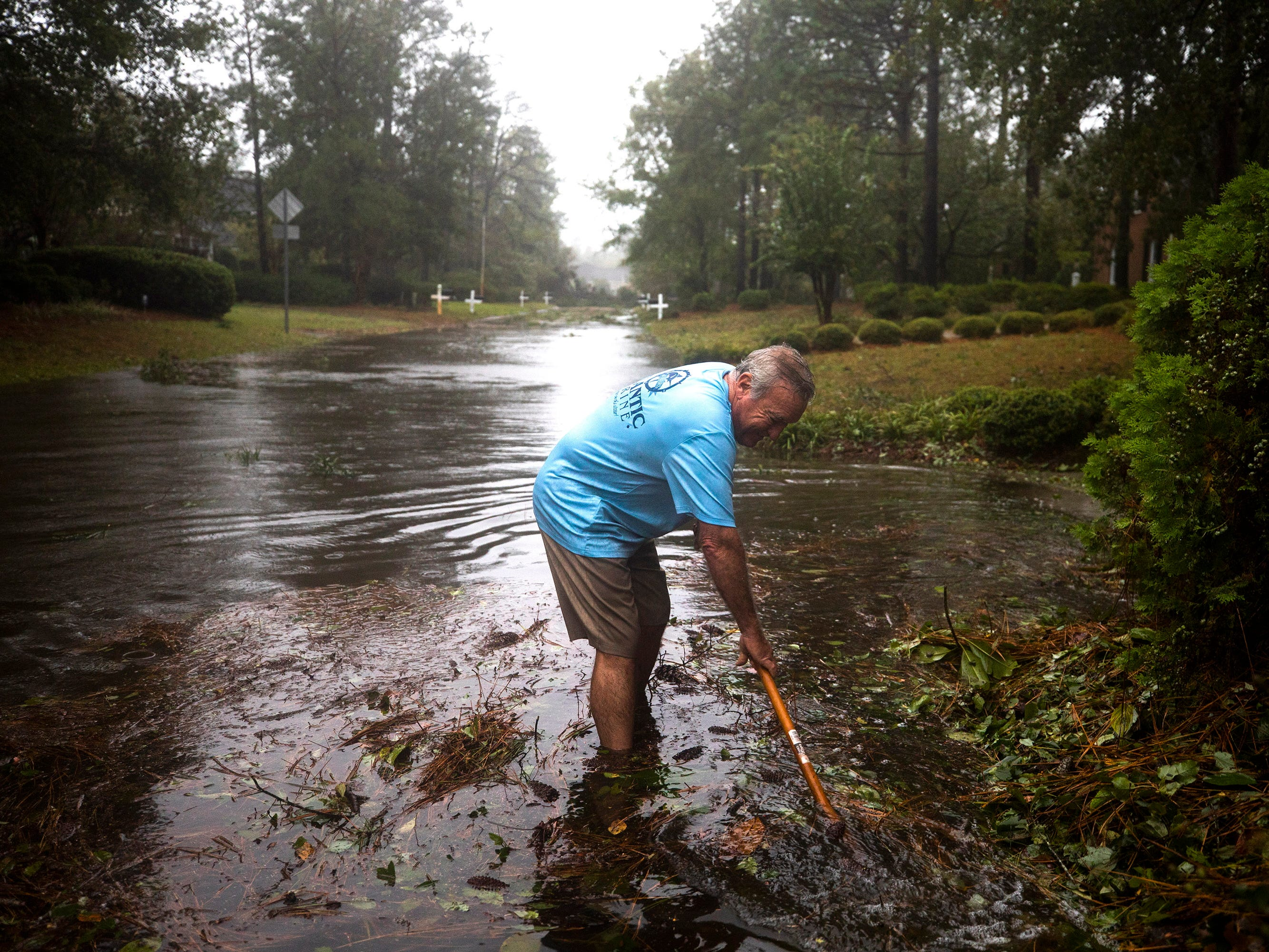 Barry Shape attempts to clear debris from a storm drain as Hurricane Florence comes ashore in Wilmington, N.C. Sept. 14, 2018.