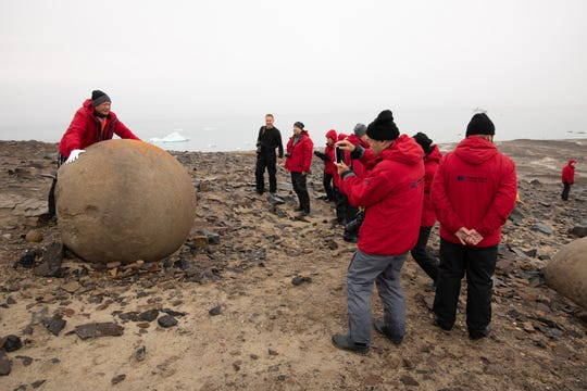 At rugged Champ Island, part of Franz Josef Land, Bremen passengers pose for pictures with what are billed as the biggest geodes in the world.