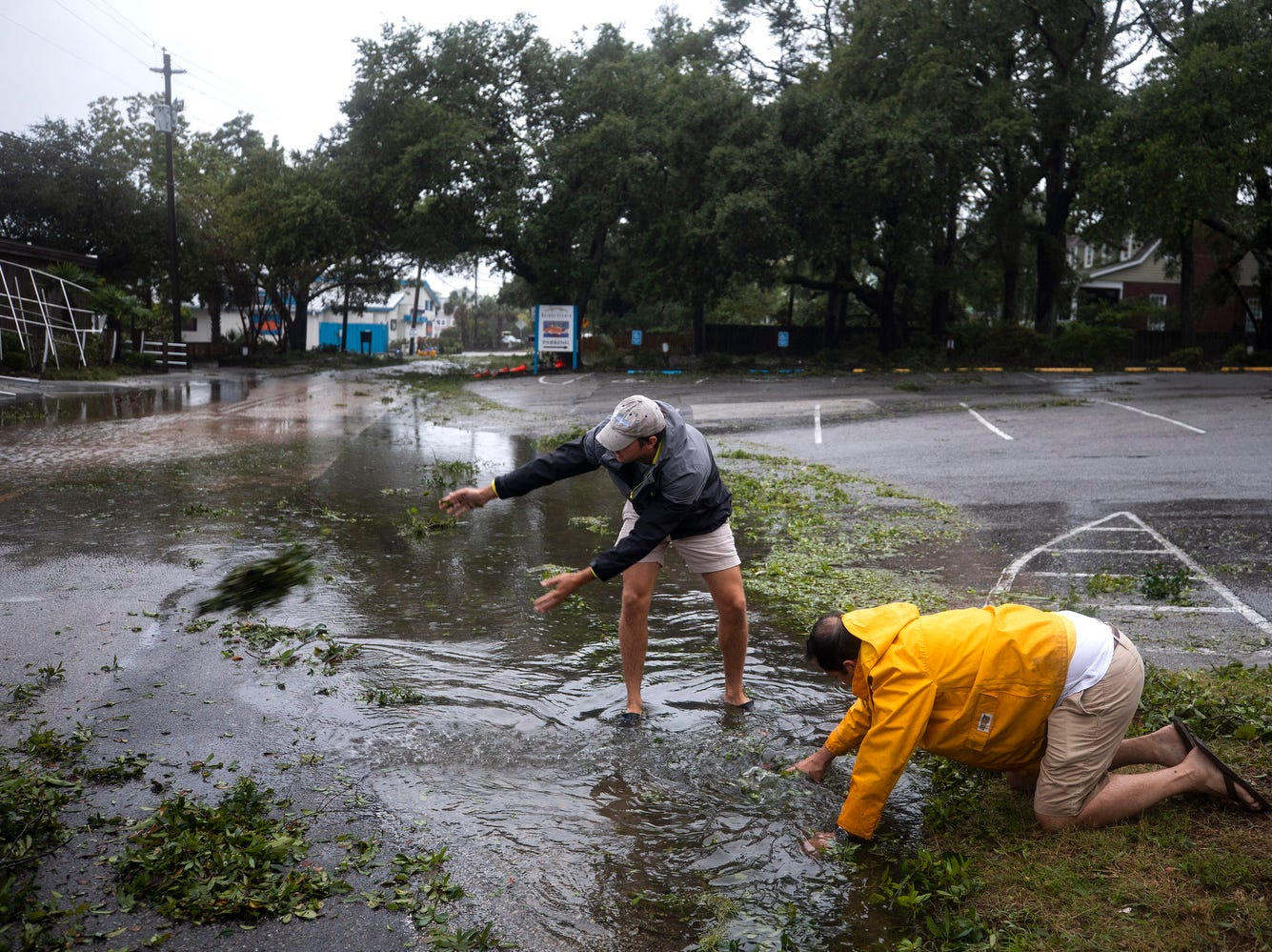 Jay Baker (R) and Chris Floyd (L) attempt to clear debris from a storm drain as Hurricane Florence comes ashore in Wilmington, N.C..