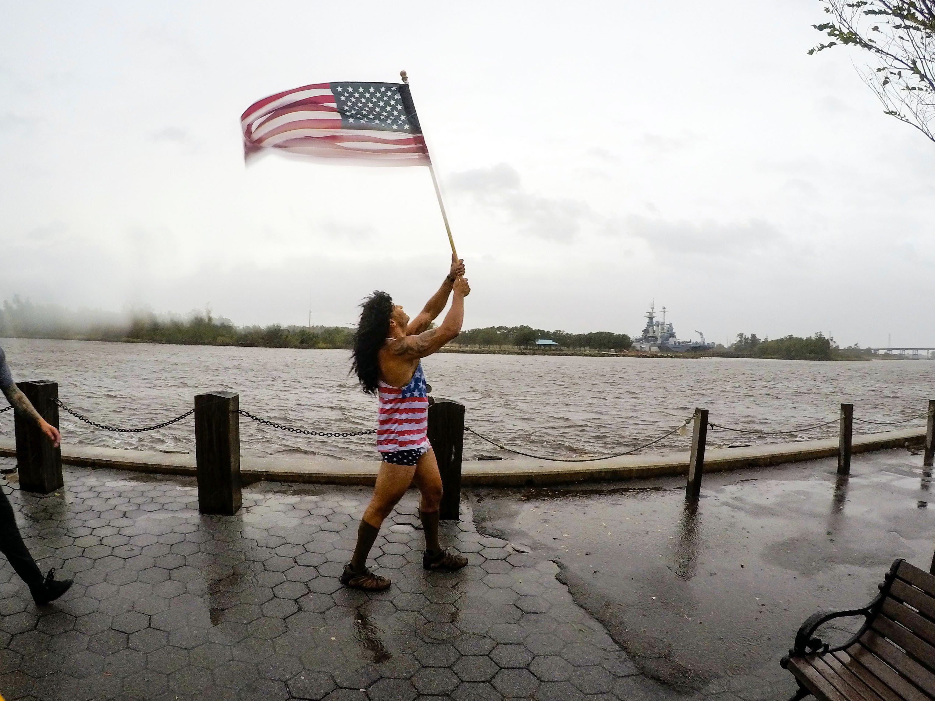 Jeff Egyp carries a United States flag in windy conditions along the Cape Fear River in Wilmington, N.C.