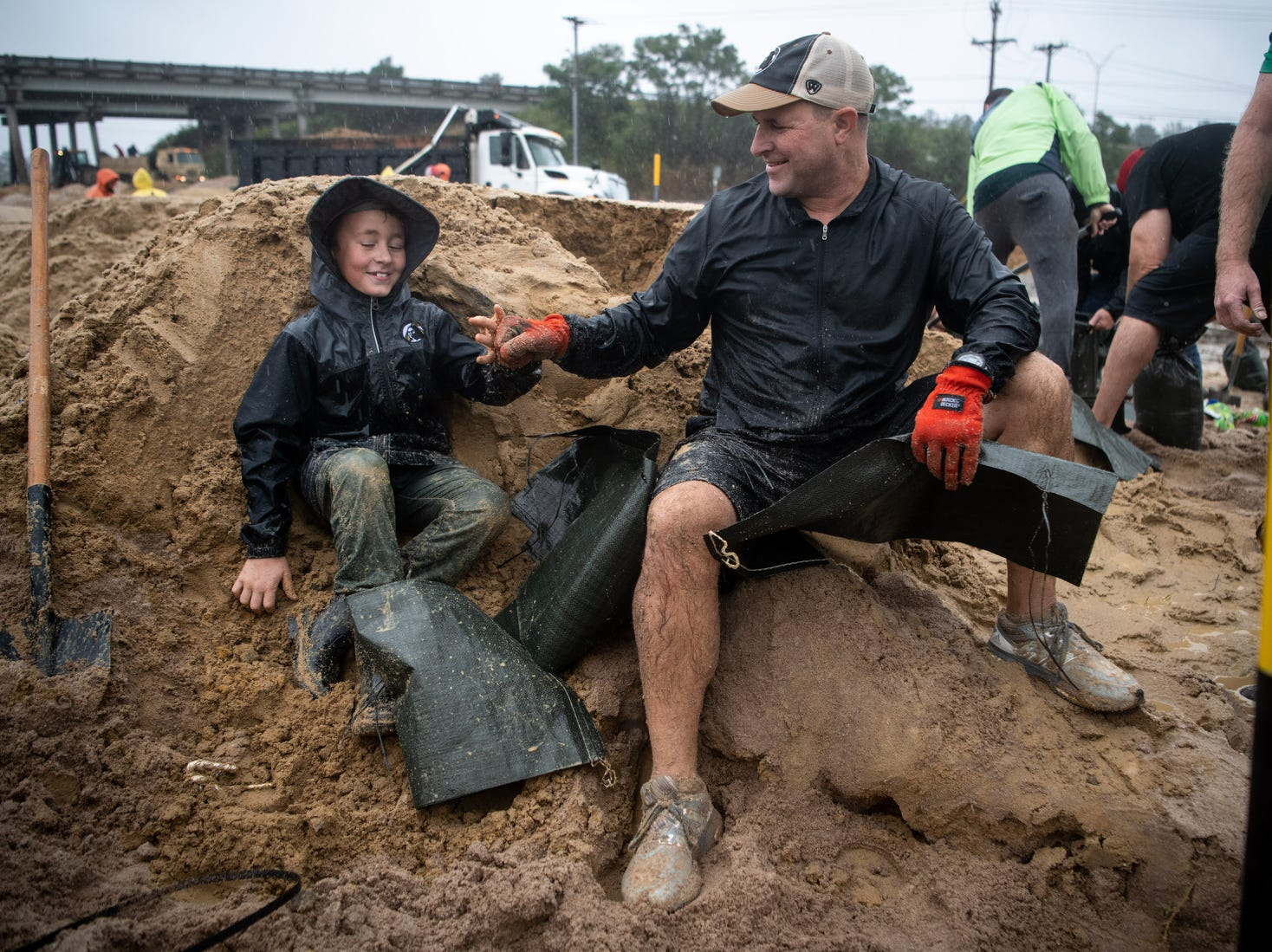 Volunteers Rivers Malcolm, left, 9, and Ben Miller, right, bump fists while filling sandbags to help reinforce a low-lying area in Lumberton, N.C..
