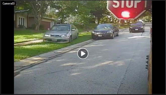Video captured a driver swerving into a lawn and speeding past a stopped school bus on Wednesday. Police say they arrested the driver, who has a suspended license and criminal history.