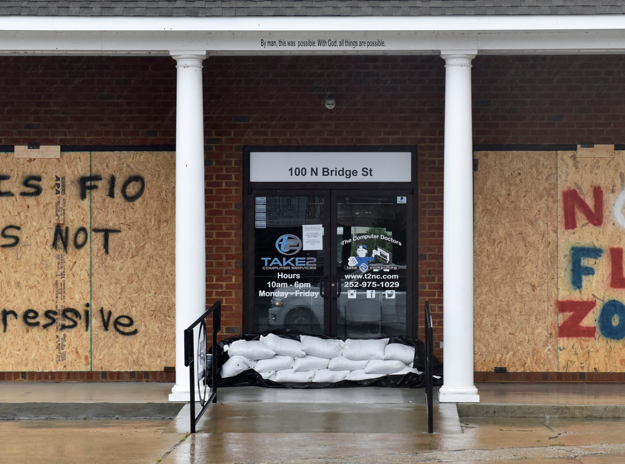 A computer store boarded up its windows on the corner of Main St and Bridge St in Washington, N.C. on Friday morning.