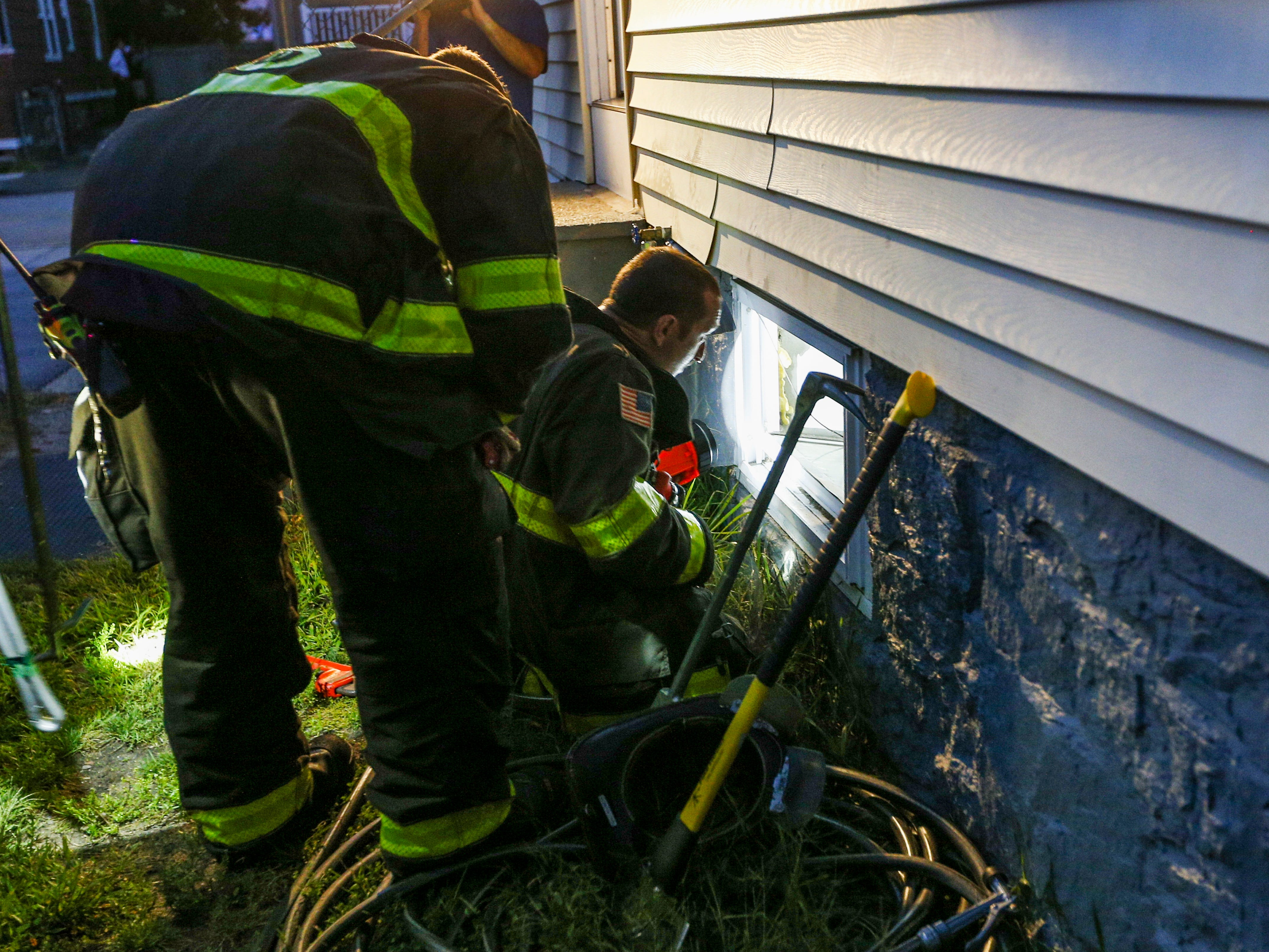 Firefighters gain entrance into a house through a basement window to check the gas line in Lawrence, Mass.