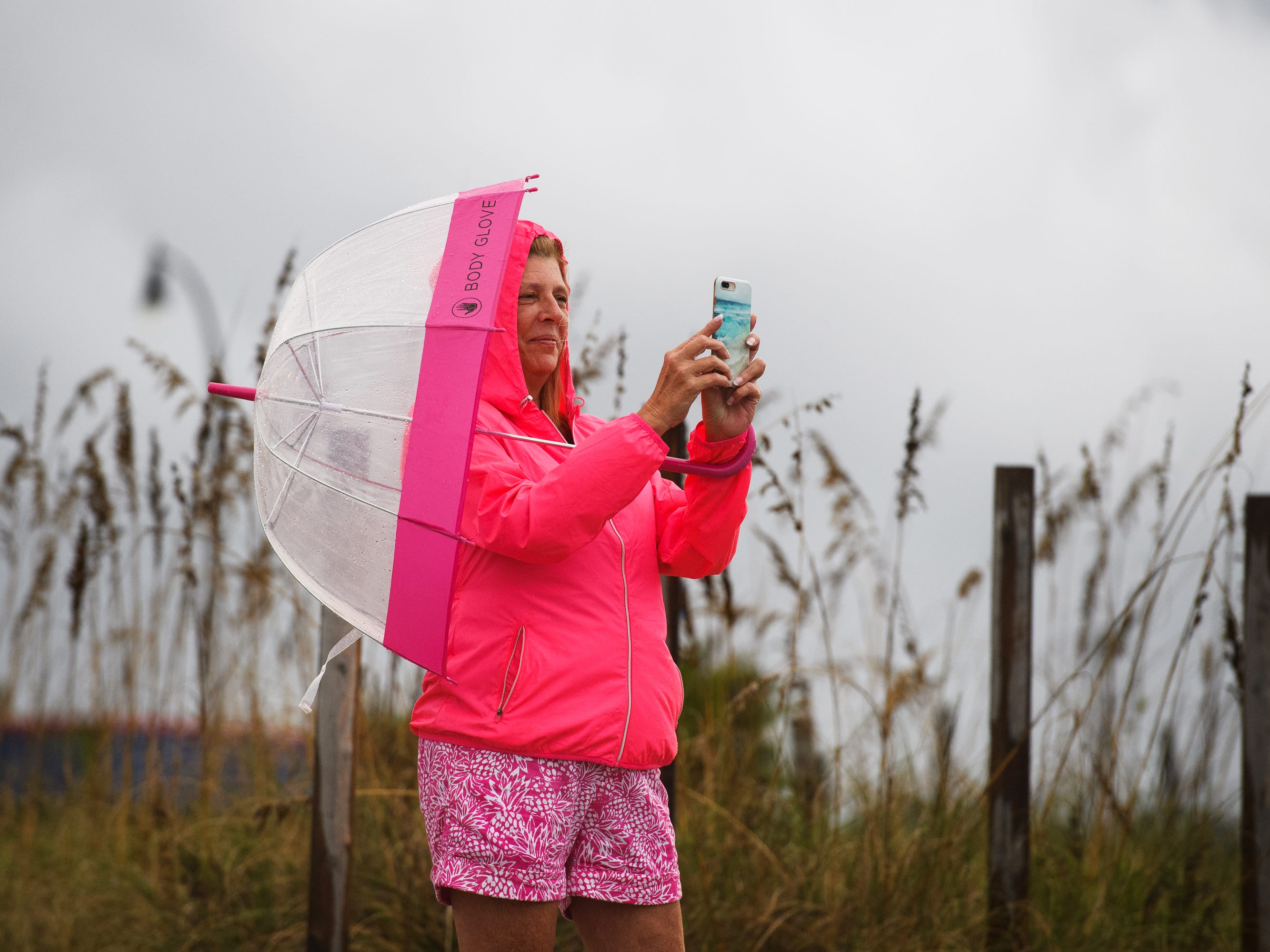 Karen Glass takes photos of the the shore at Cherry Grove Beach, S.C. after the first rain from an outer band of Hurricane Florence hits the area on Sept. 13, 2018. (
