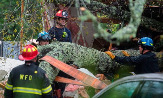 Firefighters work to remove a tree that fell on a house during  Hurricane Florence in Wilmington, N.C., Friday.