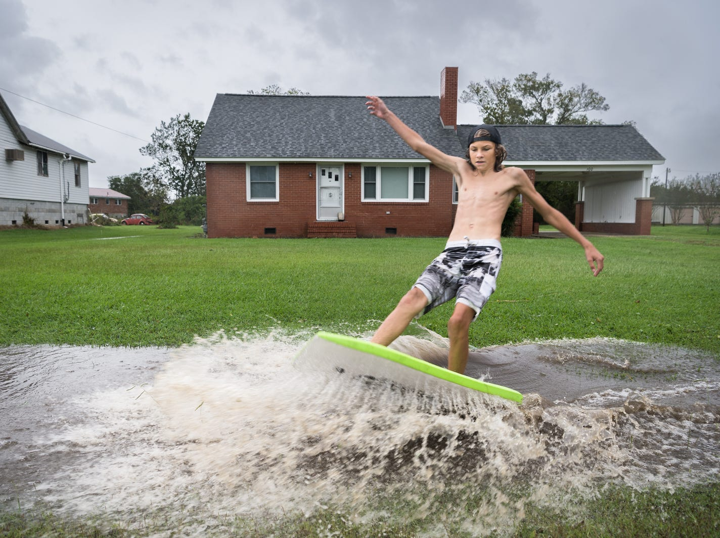 Somebody's having fun.  Deacon Etheridge, 14, surfs on a large puddle on Main Street in Swan Quarter, N.C., Friday,  after Hurricane Florence made landfall.