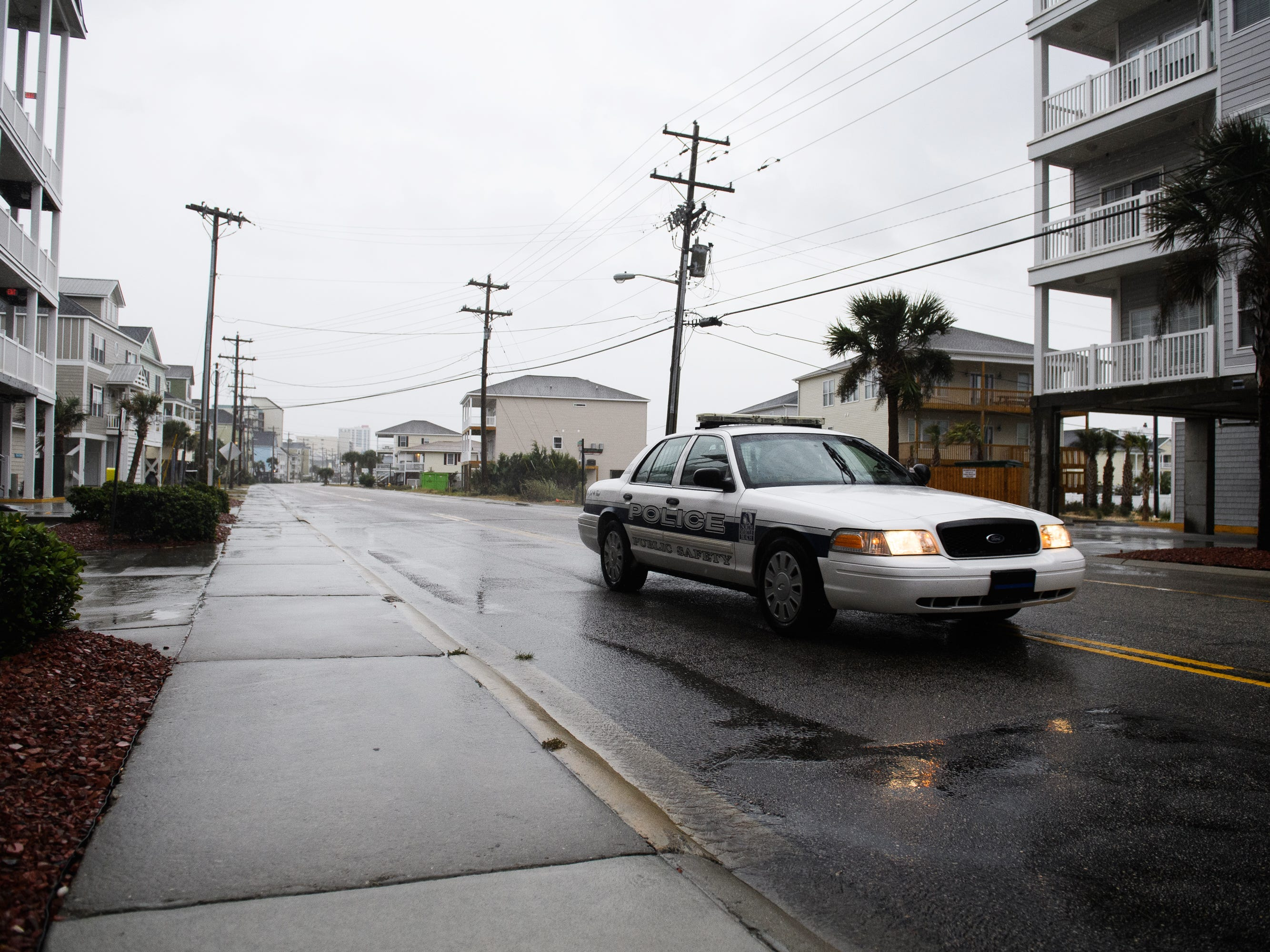A North Myrtle Beach Public Safety officer drives down North Ocean Boulevard as the first rain from an outer band of Hurricane Florence hits the Cherry Grove Pier area of North Myrtle Beach, S.C. on Sept. 13, 2018.