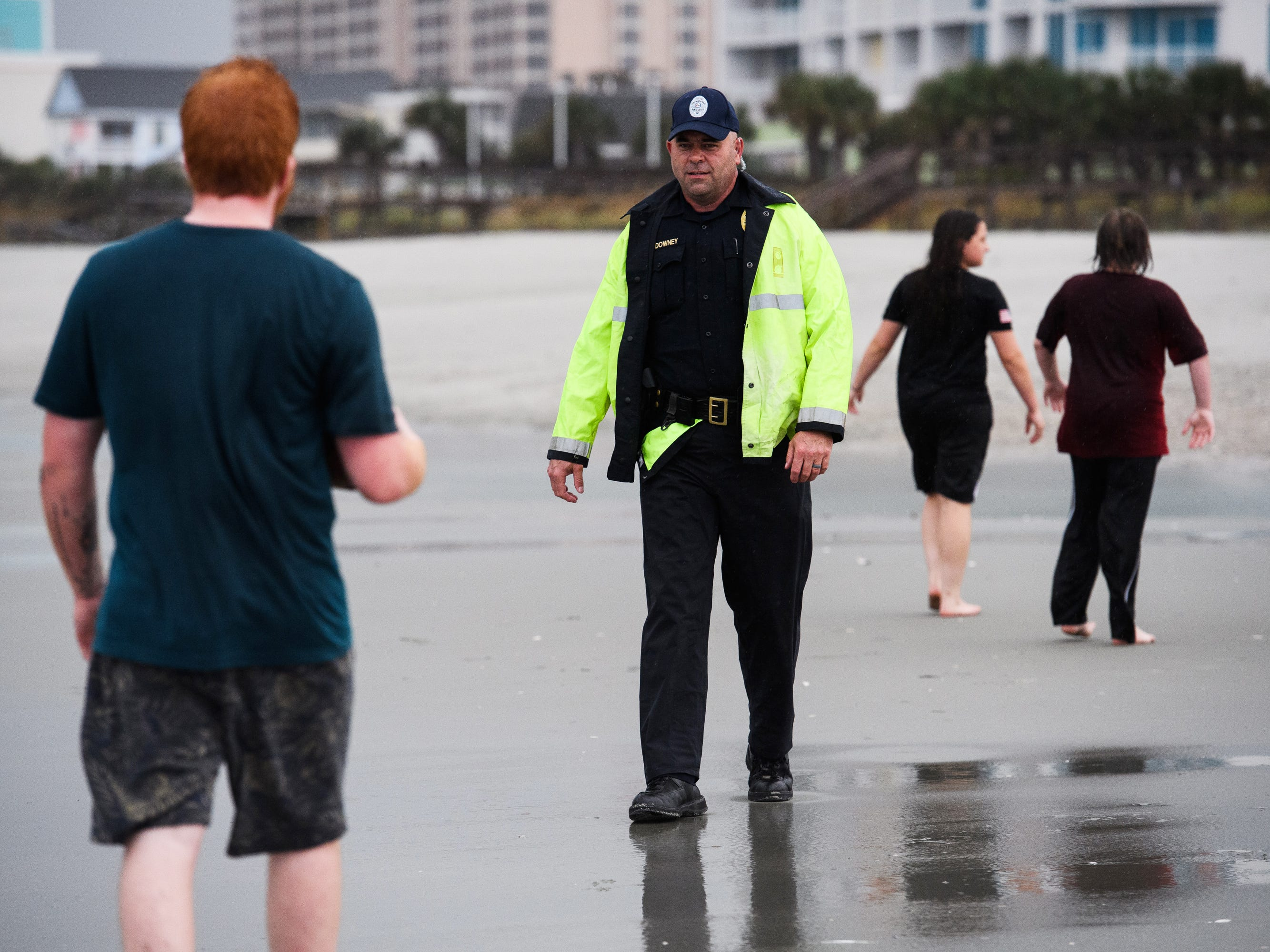 A North Myrtle Beach, S.C. public safety officer informs beachgoers of the 7 p.m. curfew due to Hurricane Florence on, Sept. 13, 2018.