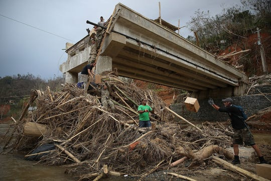 Members of the U.S. Army 1st Special Forces Command and volunteers deliver boxes of meals and water up a makeshift ladder to people   after a bridge in Utuado, Puerto Rico, collapsed in the wake of Hurricane Maria last year. The neighborhood was cut off from help for about two weeks.