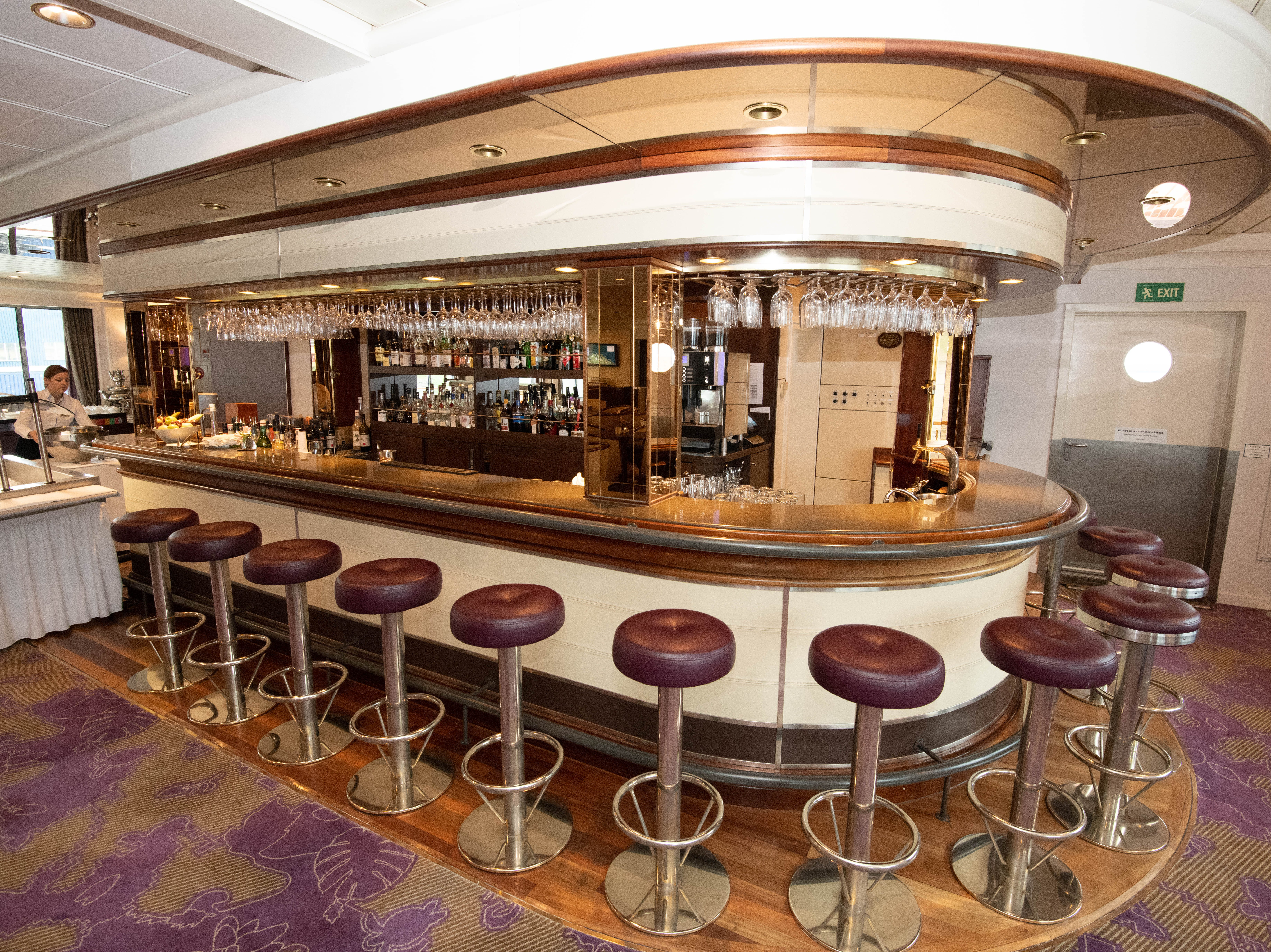 A bar with built-in stools lines the aft end of the Bremen Club.