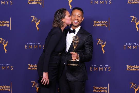 "John Legend, winner of the award for outstanding variety special for ""Jesus Christ Superstar Live in Concert,"" gets a kiss from wife Chrissy Teigen at the 2018 Creative Arts Emmy Awards on Sept. 9, 2018 in Los Angeles."