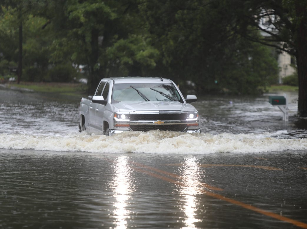 A truck drices through a flooded River Rd. in Washington Park, N.C., on Friday