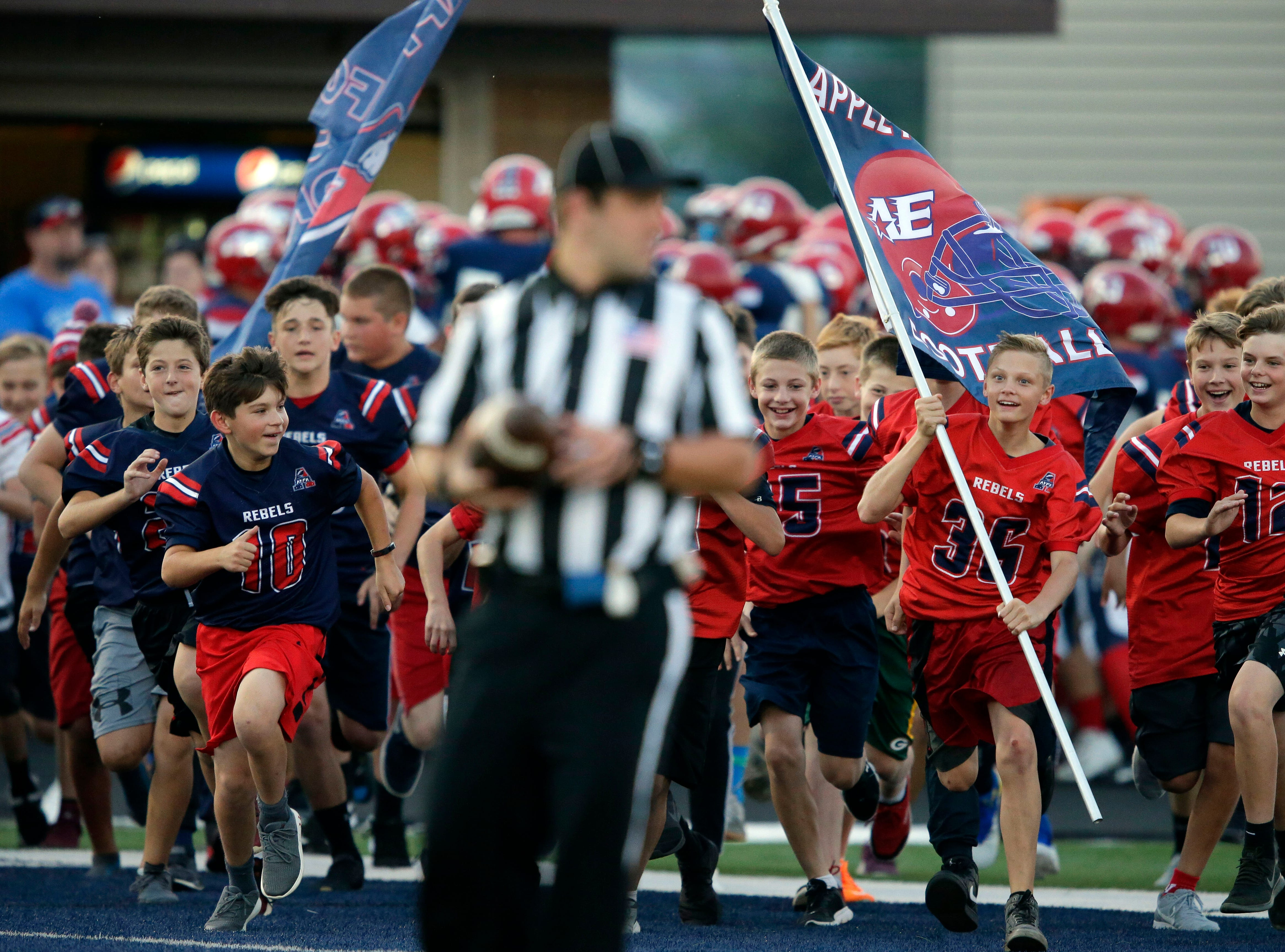 Young football players charge the field in front of the Appleton East Patriots before an unsuspecting referee dashes out of the way as the Patriots take on Appleton North in a Valley Football Association game Friday, September 14, 2018, at Appleton East High School in Appleton, Wis.Ron Page/USA TODAY NETWORK-Wisconsin