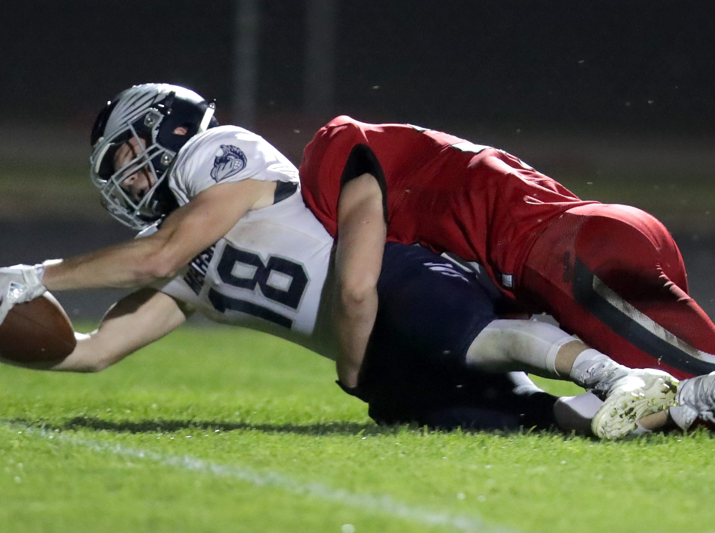 Menasha High School's #18 Riley Zirpel rushes for a second half touchdown against New London High School's #24 Sean Cortright during their football game on Friday, September 14, 2018, New London, Wis. Menasha defeated the Bulldogs 34 to 28.