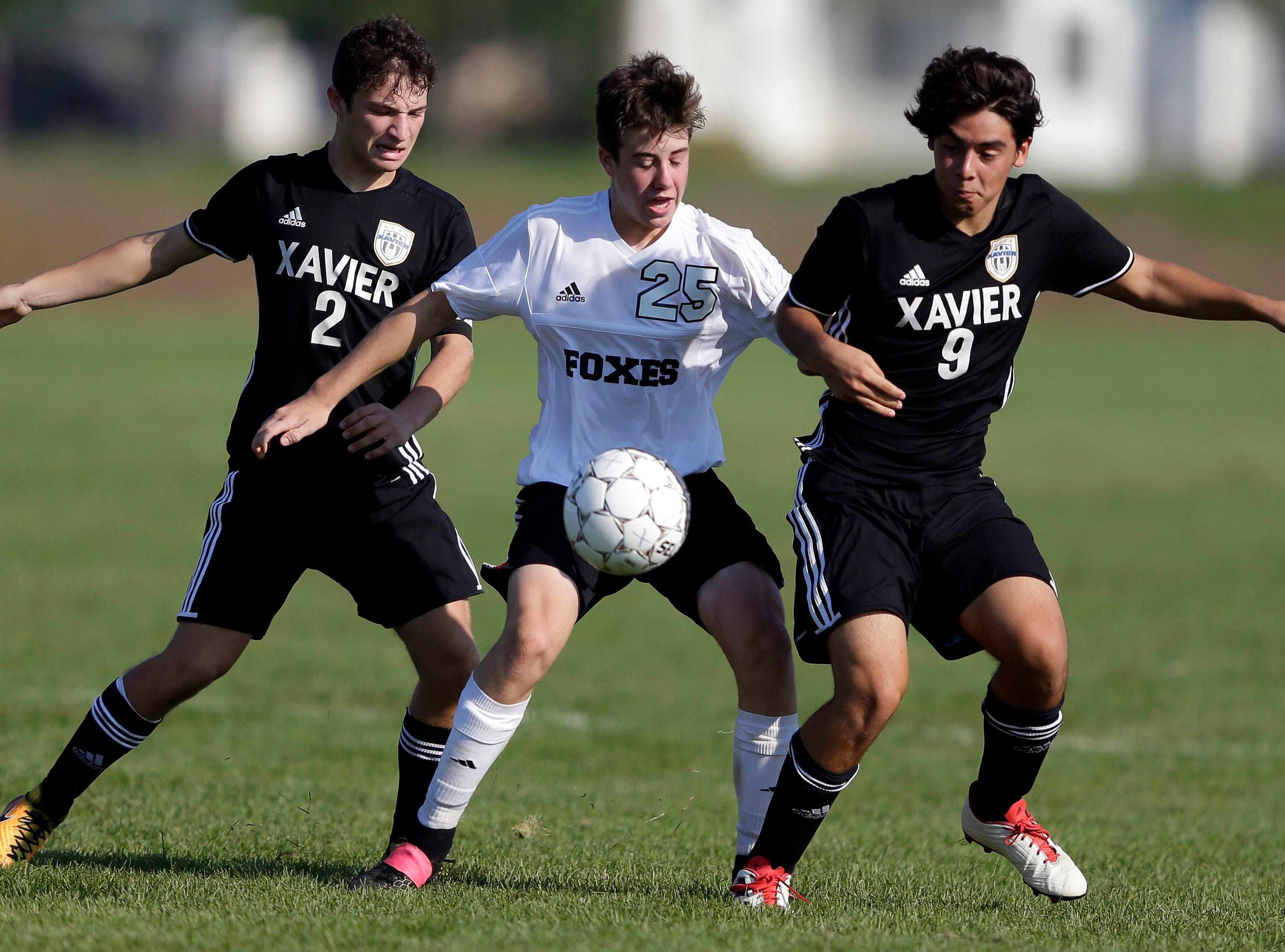 William Mleziva, left, and Alex Lopez, right of Xavier work against Addison Fett of Fox Valley Lutheran in the Xavier boys soccer tournament Saturday, September 15, 2018, at the Scheels USA Sports Complex in Appleton, Wis.