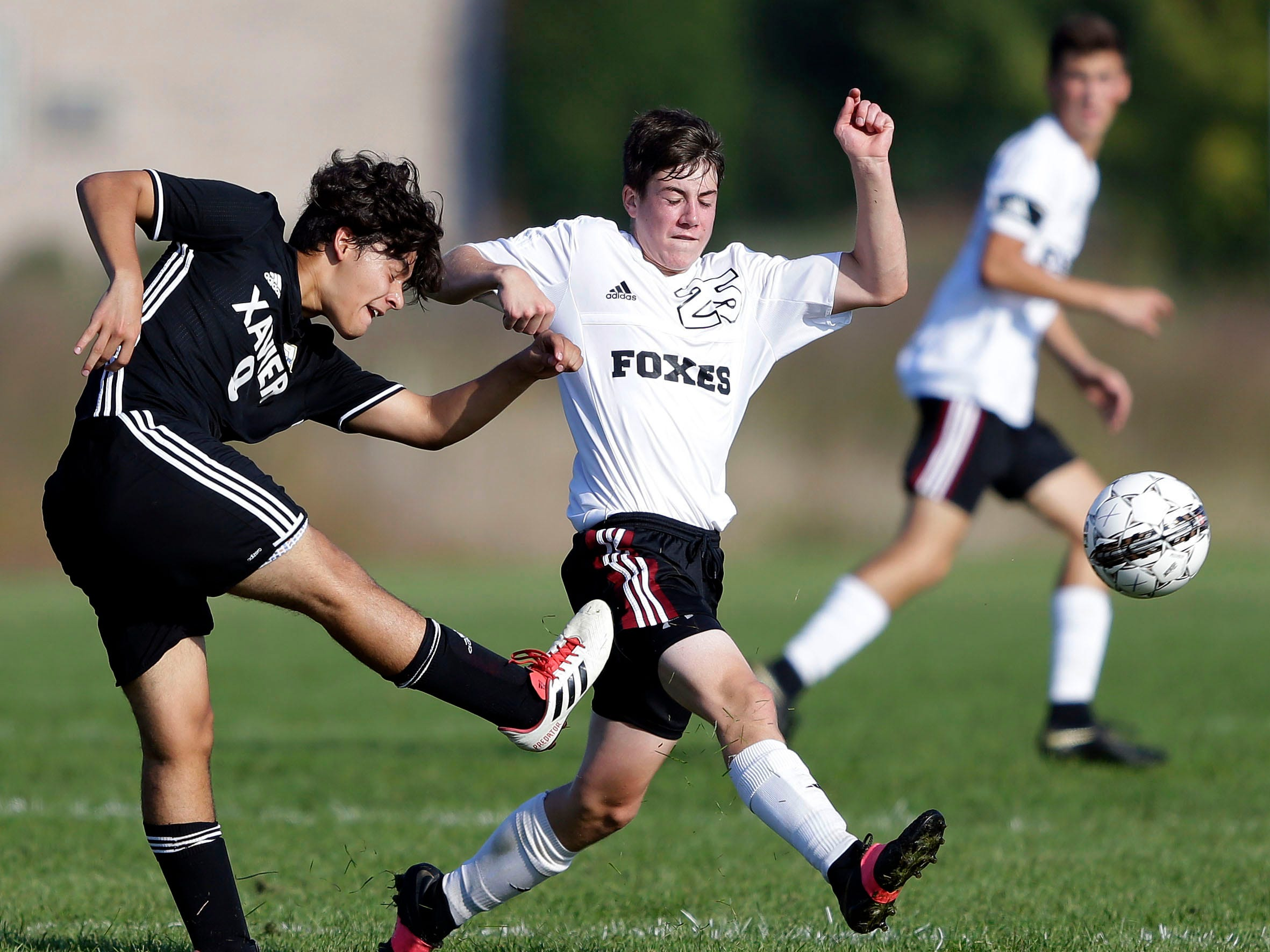 Alex Lopez, left, of Xavier passes while being defended by Addison Fett of Fox Valley Lutheran in the Xavier boys soccer tournament Saturday, September 15, 2018, at the Scheels USA Sports Complex in Appleton, Wis.