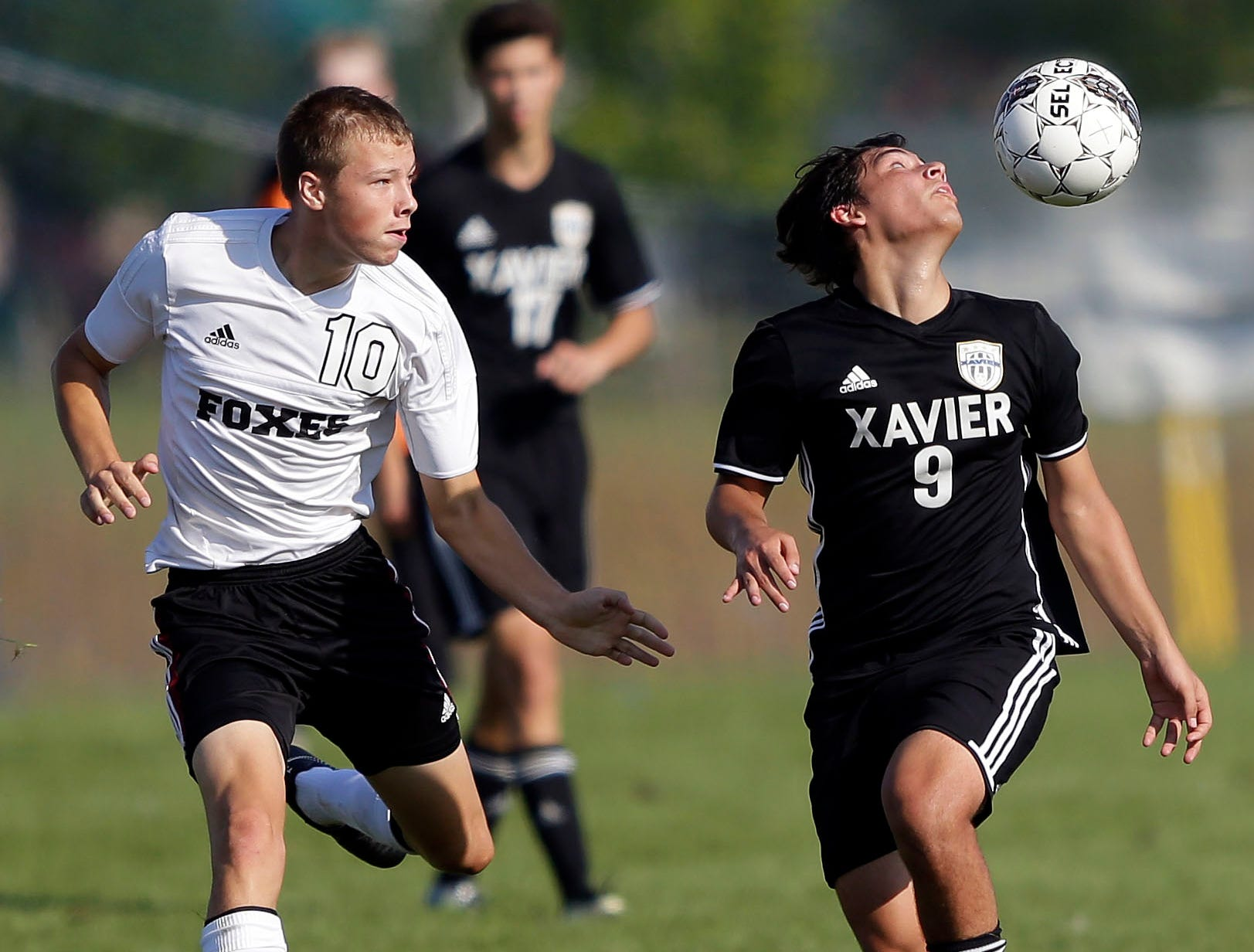 Daniel Plitt, left, of Fox Valley Lutheran and Alex Lopez of Xavier keep an eye on the ball in the Xavier boys soccer tournament Saturday, September 15, 2018, at the Scheels USA Sports Complex in Appleton, Wis.