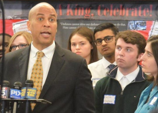 Sen. Cory Booker speaks while Zach Dougherty and Sarah Emily Baum stand by his side.
