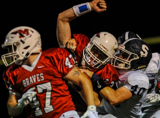 Dale Sieczkowski of Manalapan, is tackled by Middletown South's Matt Tardy during a game in Manalapan on Sept. 14, 2018.