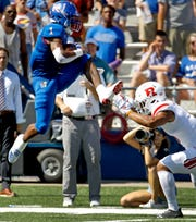 Kansas running back Pooka Williams Jr. (1) leaps over Rutgers defensive back Isaiah Wharton (11) as he runs the ball during the first half of an NCAA college football game Saturday, Sept. 15, 2018, in Lawrence. (AP Photo/Charlie Riedel)