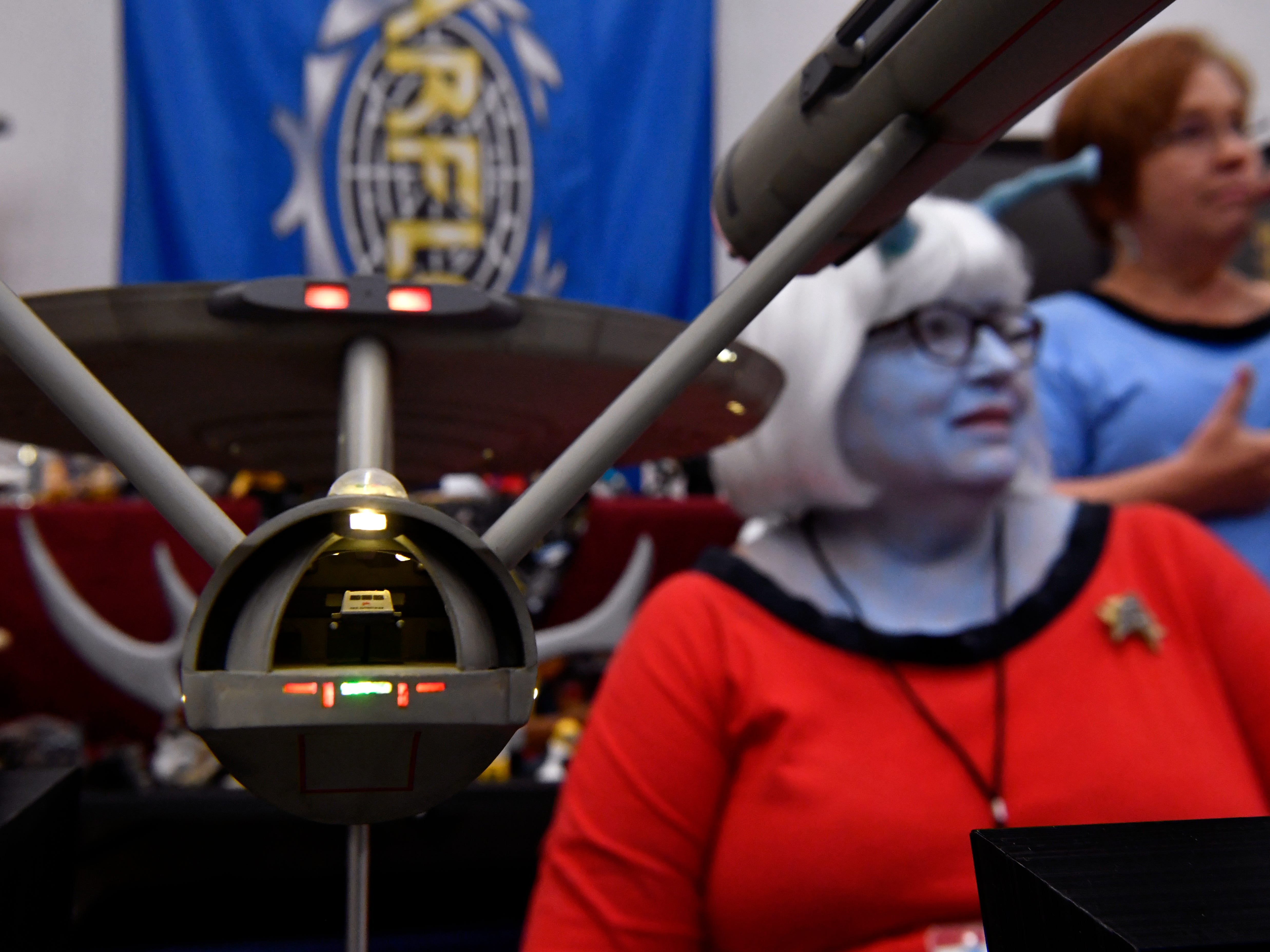 A tiny shuttlecraft can be seen inside the custom-built USS Enterprise beside Glenda Stephenson, dressed in blue makeup as an Andorian, at the USS Diamondback booth Saturday Sept. 15, 2018 in the Abilene Convention Center. The group of Star Trek fans and other science fiction shows were part of the Anime Sekai convention Saturday.