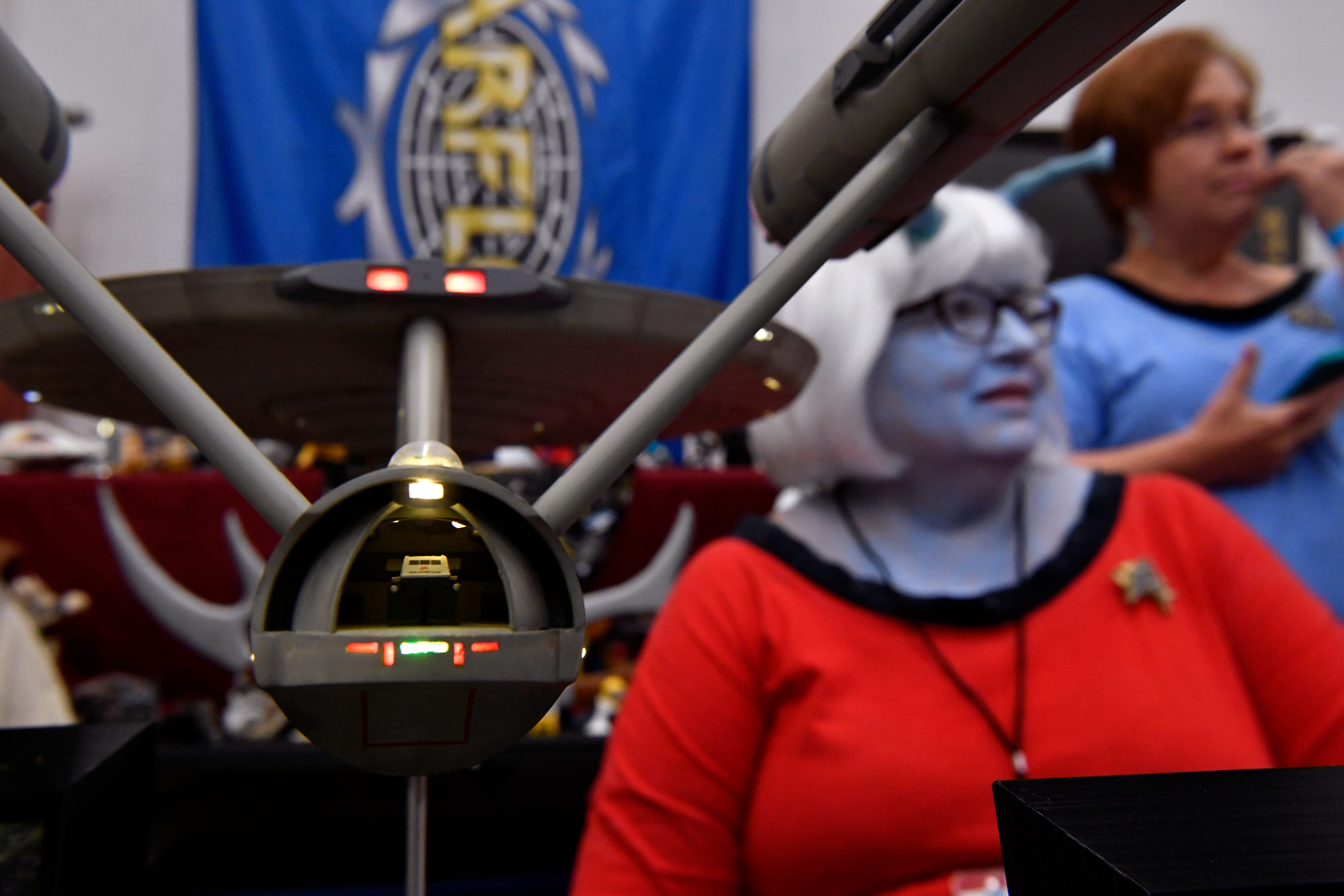 """A tiny shuttlecraft can be seen inside the custom-built USS Enterprise beside Glenda Stephenson, dressed in blue makeup as an Andorian, at the USS Diamondback booth Saturday at the Abilene Convention Center. The group of """"Star Trek"""" fans and other science fiction shows were part of the Anime Sekai convention."""