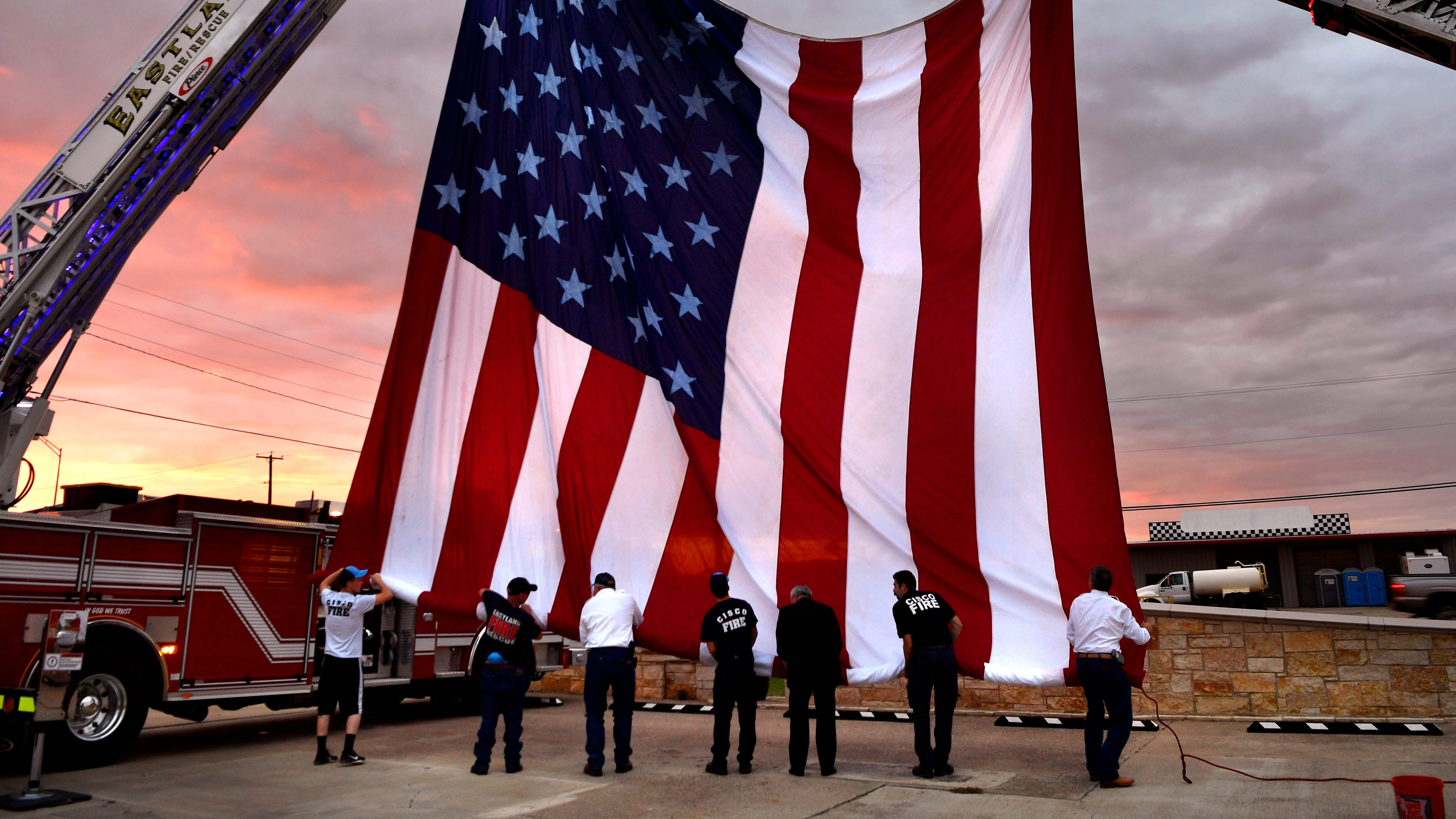 Eastland County firefighters roll a 30-by-60-foot American flag at the conclusion of a 9/11 Remembrance Day service sponsored by the Eastland County Republican Party Tuesday Sept. 11, 2018. The event was held at the River of Life Church youth center.