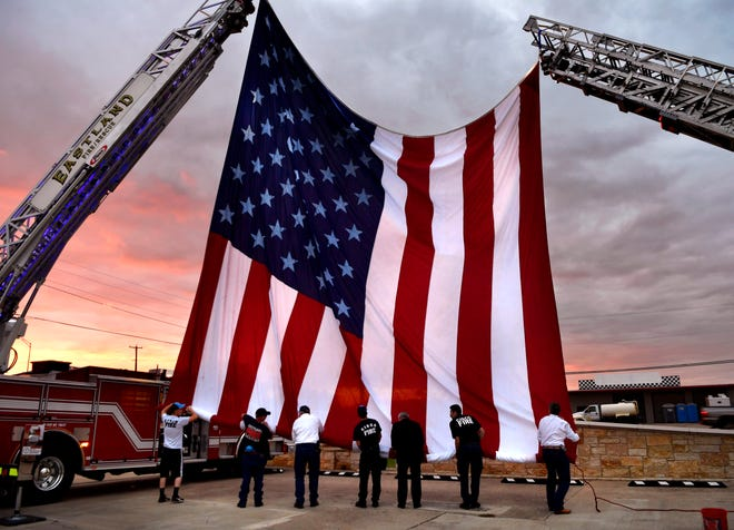 Eastland County firefighters roll a 30-by-60-foot American flag at the conclusion of a 9/11 Remembrance Day service sponsored by the Eastland County Republican Party on Sept. 11. The event was held at the River of Life Church youth center.