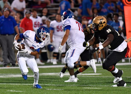 Cooper's Daelin Campos eyes Eagles defensive lineman Tygee Gambrell while running the ball downfield during Friday's Crosstown Showdown Sept. 14, 2018. Abilene won, 20-13.
