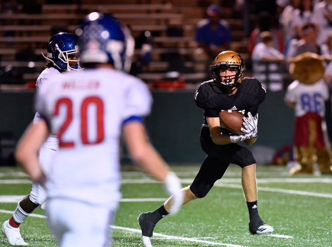 Abilene wide receiver Clay Cox catches a pass while eyeing Cooper linebacker Brady Miller during Friday's Crosstown Showdown Sept. 14, 2018. Abilene won, 20-13.
