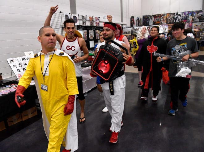 """Fred """"Deaconrap"""" Pacheo (in yellow) leads a group of cosplayers and anime enthusiasts in a brief procession around the convention floor. The inaugural Anime Sekai convention at the Abilene Convention Center ends Sunday."""
