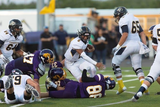 From left,  Wylie defenders Dayton Barnes, Canon Hanna and Brody Baker take down Stephenville quarterback Cole Stanley on Friday evening during a non-district matchup at Bulldog Stadium.