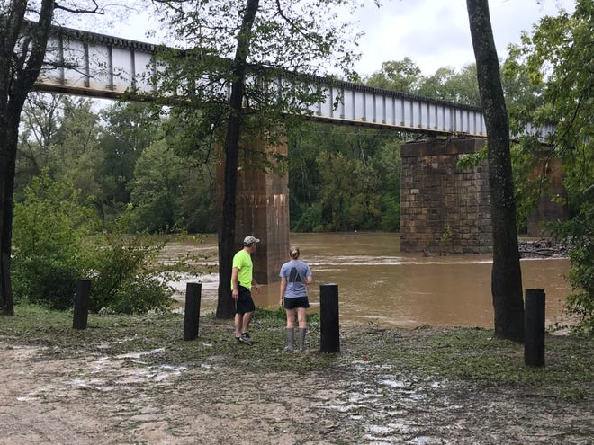 Ryan and Heather Roscoe look at the rising waters of the Cape Fear River Saturday in Fayetteville, North Carolina.  The river reached above the railroad trestle's stone columns during floods from Hurricane Matthew in 2016. The river is expected to swell higher than that by Tuesday.