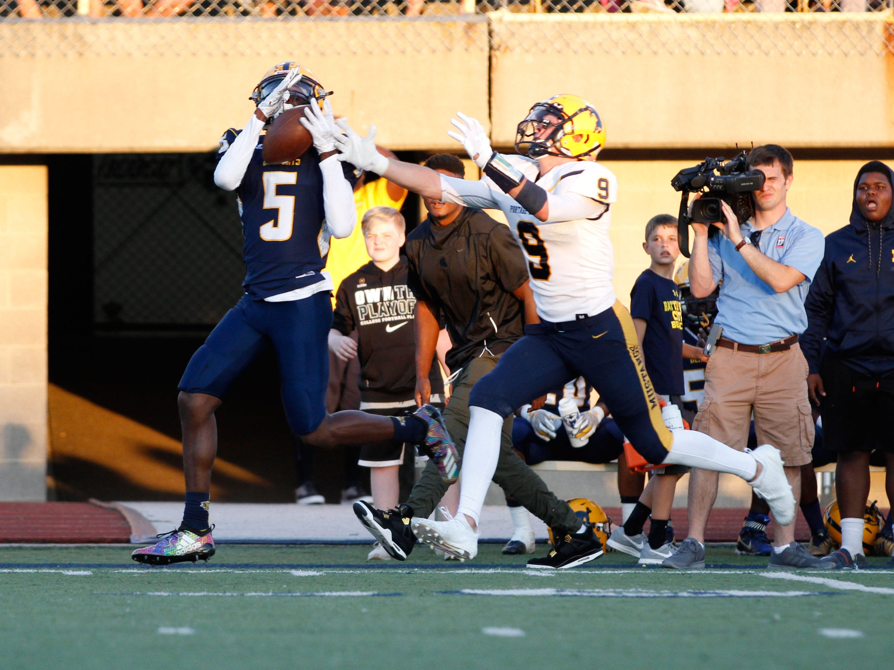 Battle Creek Central's KeOndre Glass makes a catch over Luke Leto of Portage Central in first half action.