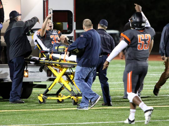 Central Kitsap's Eathan Dodson signals to teammates after breaking his ankle during Central Kitsap's game against Yelm.