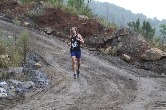 Duncan Reuning, who finished first in the Rock the Quarry Trail Challenge 5K on Sept. 15, makes is way into the mouth of the quarry as a light drizzle begins to fall.