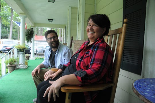 My Place Inn owner Frank Cappelli and innkeeper Amanda Blamowski sit on the front porch of the Black Mountain bed and breakfast that offered free rooms for people who were fleeing Hurricane Florence.