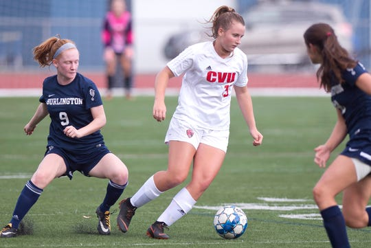 Champlain Valley's Olivia Morton, center, dribbles away from pressure by Burlington's Helen Worden (9) during Saturday's high school girls soccer game at Buck Hard Field on Sept. 15, 2018.