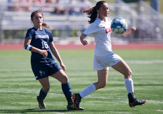Burlington's Sage Smith, left, sends a pass around Champlain Valley's Jess Klein during Saturday's high school girls soccer game at Buck Hard Field on Sept. 15, 2018.