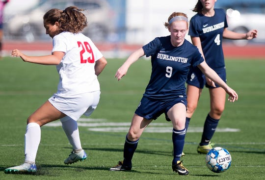 Burlington's Helen Worden, right, dribbles past Champlain Valley's Shelby Statton during Saturday's high school girls soccer game at Buck Hard Field on Sept. 15, 2018.