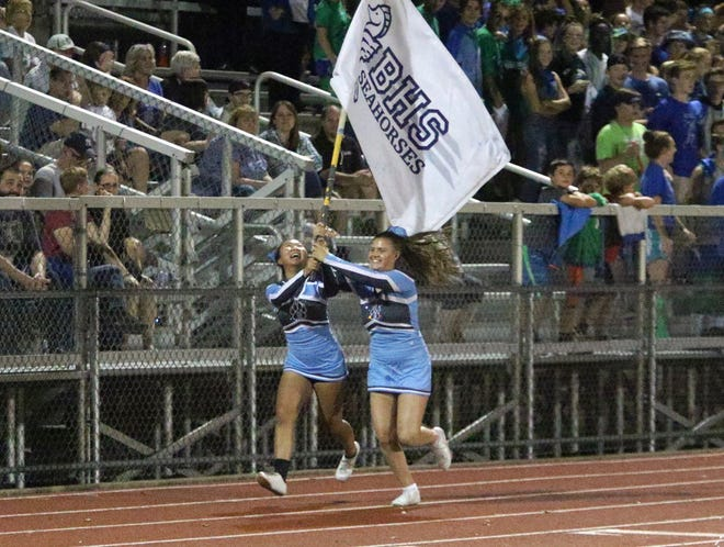 SeaWolves cheerleaders Yu Xin Zhao and Haley Drown make a flag run in front of spectators watching the South Burlington/Burlington football team make it's debut at Burlington's Buck Hard Field.